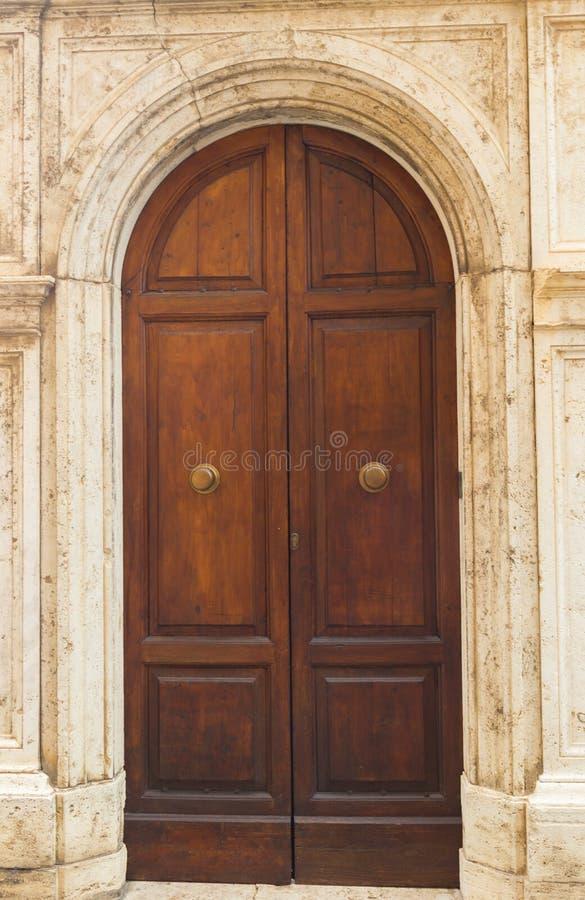 De oude houten die deur in Siena wordt gezien stock afbeeldingen