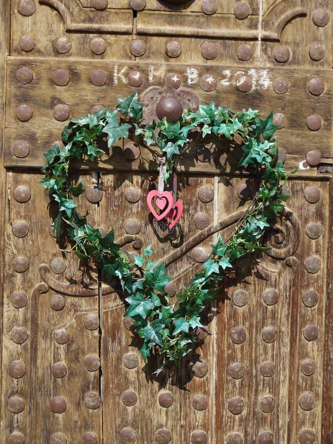De oude houten die deuren met hart worden gemaakt van doorbladert royalty-vrije stock afbeelding