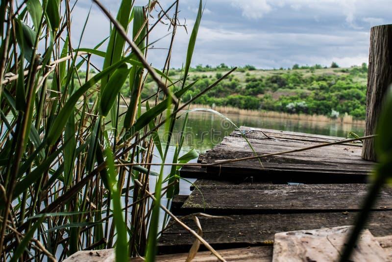 De oude, houten en sjofele brug is een kleine brug op de rivier, een plaats voor rust en stilte, royalty-vrije stock foto