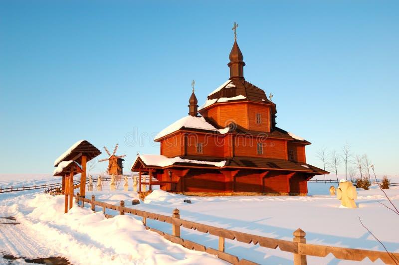 De oude houten kerk en de windmolen bij achtergrond royalty-vrije stock afbeelding