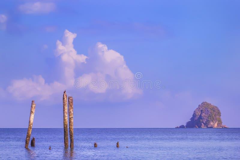 De oude houten kolommen van de vernietigde pijler bevinden zich in een kalme overzees in de stralen van zonsondergang op de achte stock foto