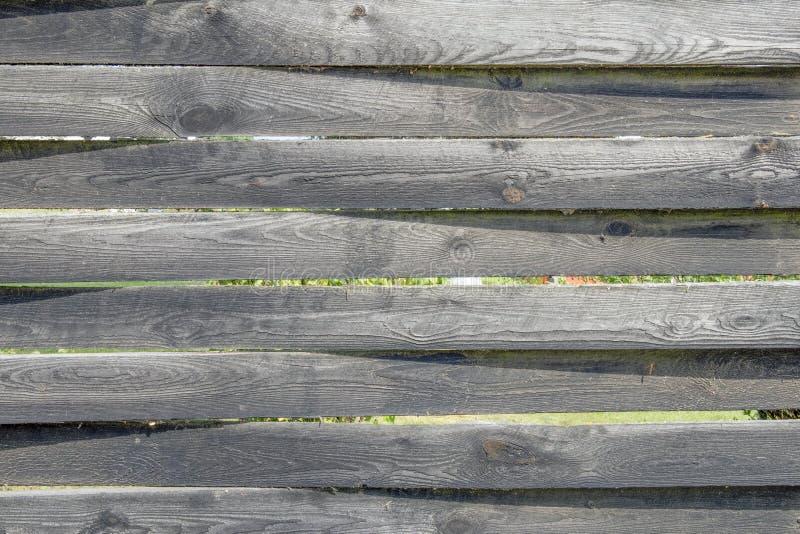 De oude houten omheining van grijs unplaned planken stock foto