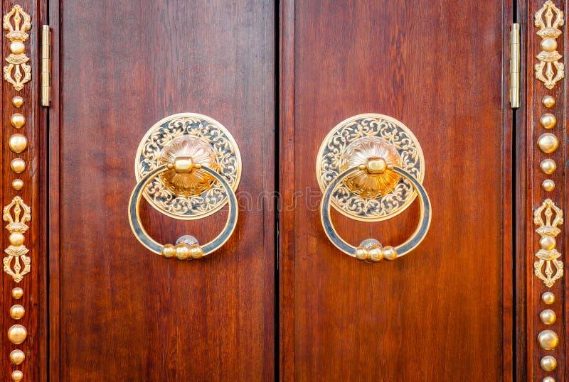 De oude houten poort met twee gouden deurkloppers belt close-up vooraanzicht Oud Deurfragment van Boeddhistische tempel Datsan stock foto