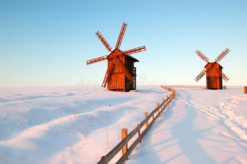 De oude houten windmolens tijdens zonsondergang stock foto