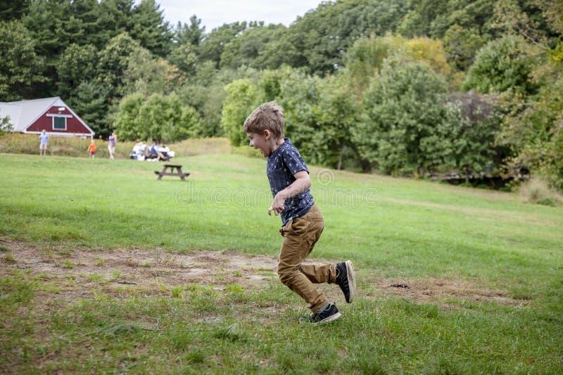 De oude jongen die van vijf jaar buiten op landbouwbedrijf lopen royalty-vrije stock foto