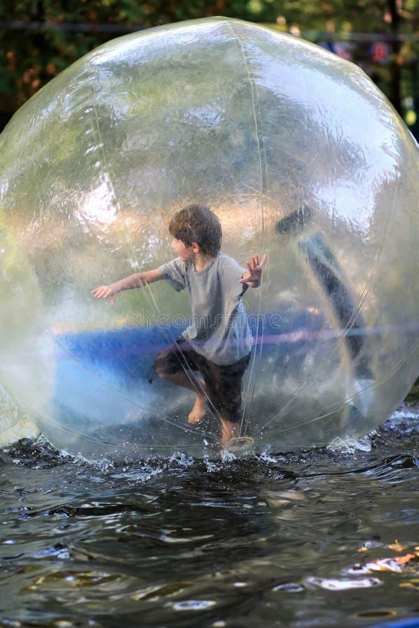 De oude jongen van vijf jaar in borrels en het grijze t-shirt in evenwicht brengen binnen een reusachtige zorbbal op het water in stock foto