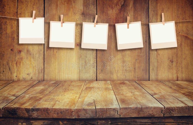 De oude kaders die van de polaroidfoto op een kabel met houten achtergrond hnaging stock afbeelding