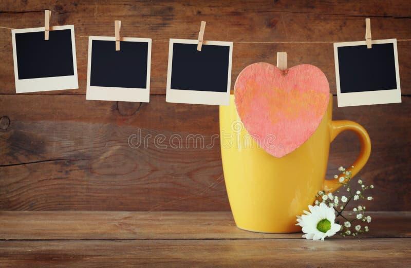 De oude kaders die van de polaroidfoto op een kabel met koffie hangen vormen en koekjes over houten achtergrond tot een kom stock foto's