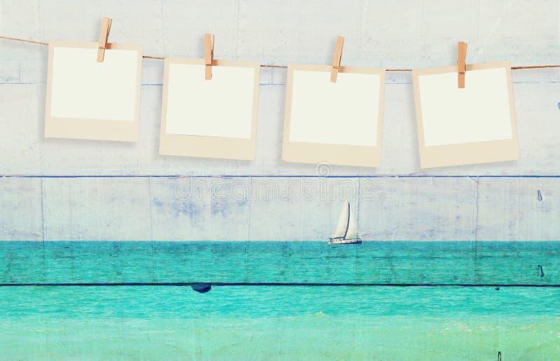 De oude kaders die van de polaroidfoto op een kabel met met dubbel blootstellingsbeeld van zeilboot bij horizon op het overzees e royalty-vrije stock foto