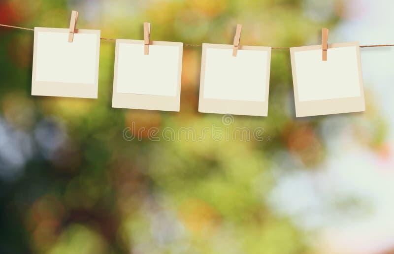 De oude kaders die van de polaroidfoto op een kabel met uitstekende houten raadslijst hangen voor de zomer onscherpe achtergrond stock foto