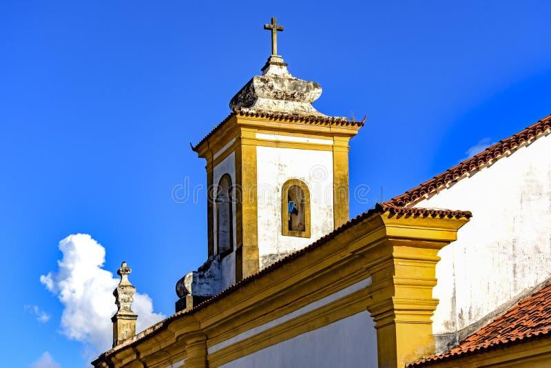 De oude katholieke toren en het kruisbeeld van de klokkerk stock foto's