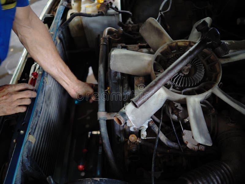 De oude koelventilatormotor van auto wordt verwijderd in garage De autoreparatiedienst Knappe glimlachende werktuigkundige royalty-vrije stock fotografie