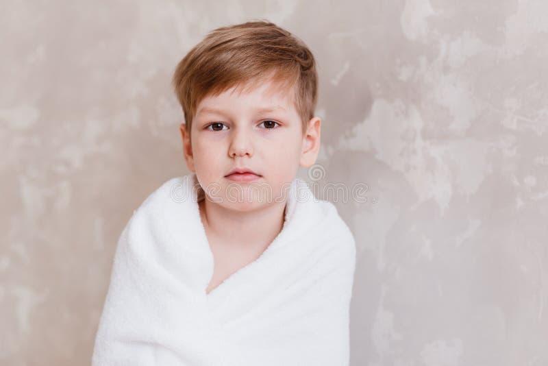 De oude leuke jongen van vijf jaar van Caucasoid die in witte Terry handdoek wordt verpakt die camera bekijkt royalty-vrije stock afbeeldingen