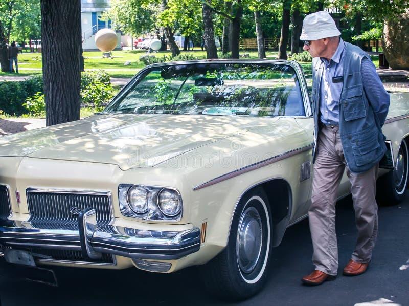 De oude man bekijkt droevig de oude gele Amerikaanse auto 1973 Oldsmobile Delta 88 Royale stock afbeeldingen
