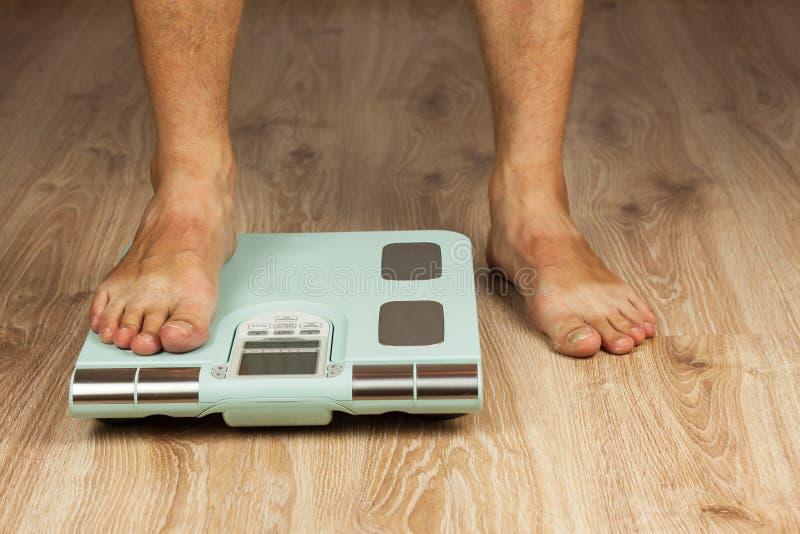De oude man bevindt zich op moderne schaal Het meten van het vetgehalte van het lichaam Intelligent medisch gewicht Het concept o royalty-vrije stock foto