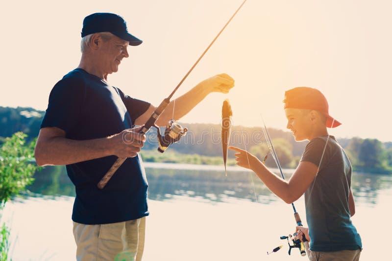 De oude man en zijn kleinzoon bevinden zich op de rivierbank De oude man ving de vissen en toont de vangst aan de jongen stock foto's