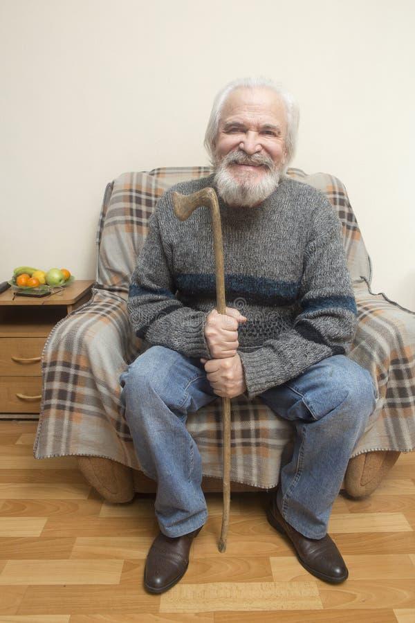 De oude man in de leunstoel thuis royalty-vrije stock foto