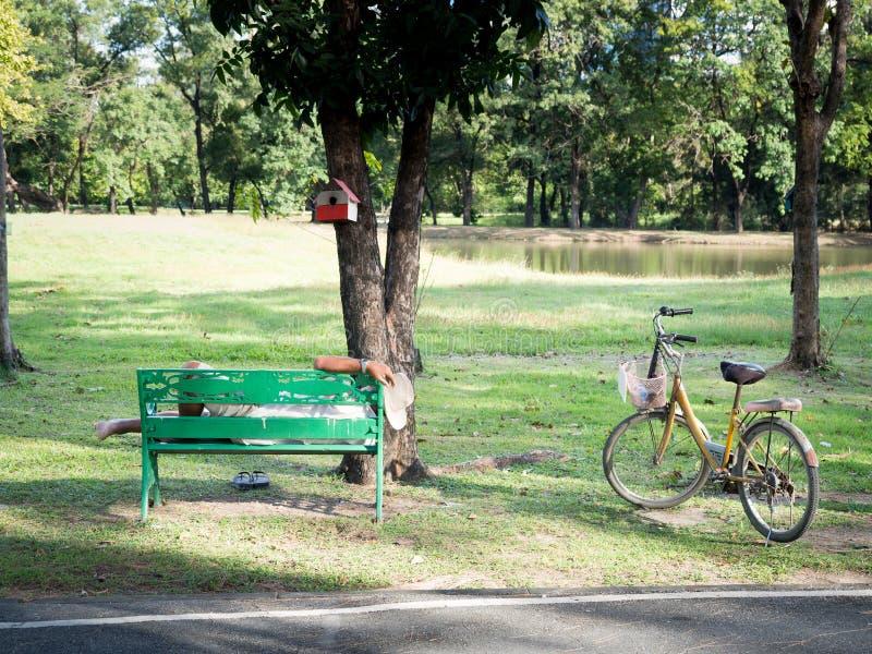 De oude man met polshorloge en het dragen van een witte cowboyhoed rustte op een groene stoel in de tuin Er is oude gele fiets stock afbeeldingen