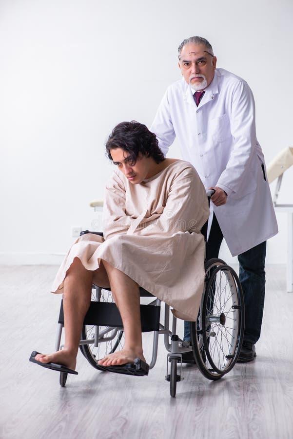 De oude mannelijke artsenpsychiater en de pati?nt in rolstoel royalty-vrije stock afbeeldingen