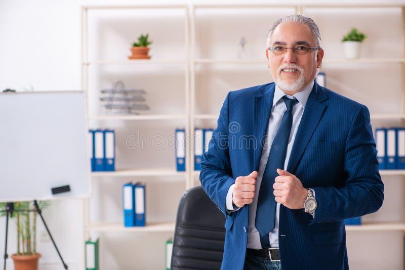 De oude mannelijke werknemer die in het bureau werken royalty-vrije stock afbeelding
