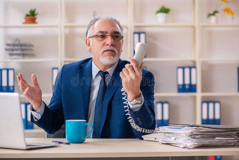De oude mannelijke werknemer die in het bureau werken stock afbeeldingen