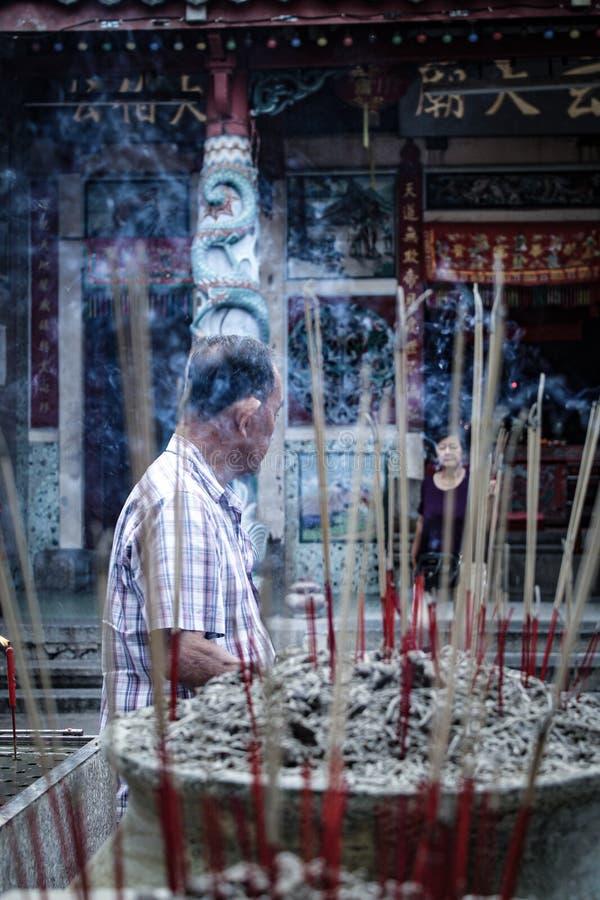 De oude mens bidt aan de god in de Chinese Tempel in Bukit Mertajam stock foto
