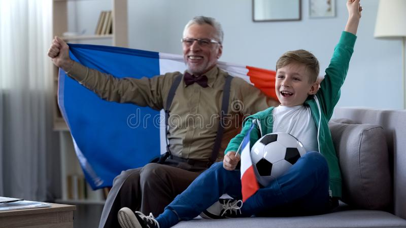 De oude mens die Franse vlag, samen met jongen houden verheugt zich overwinning van voetbalteam stock foto