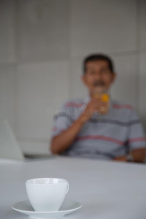 De oude mens drinkt jus d'orange voor gezond in zijn het werkruimte stock afbeeldingen