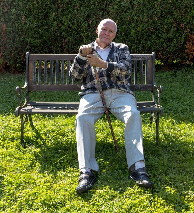 De oude mens geniet van zittend op een bank royalty-vrije stock afbeeldingen