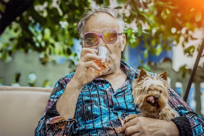 De oude mens met een hond geniet van het leven stock foto