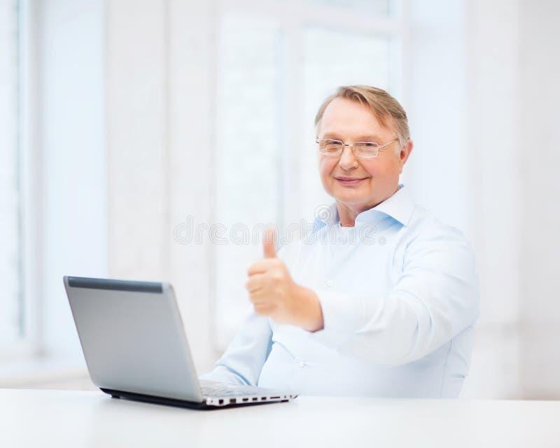 De oude mens met laptop computer het tonen beduimelt omhoog stock foto's