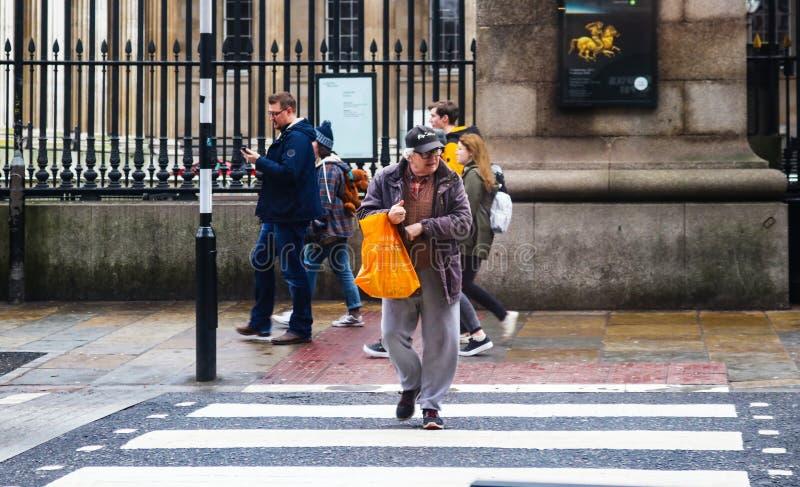 De oude mens met wit haar en sweatpants kruist weg voor British Museum met het winkelen zak - kijkend linker voor verkeer in Lo royalty-vrije stock foto's