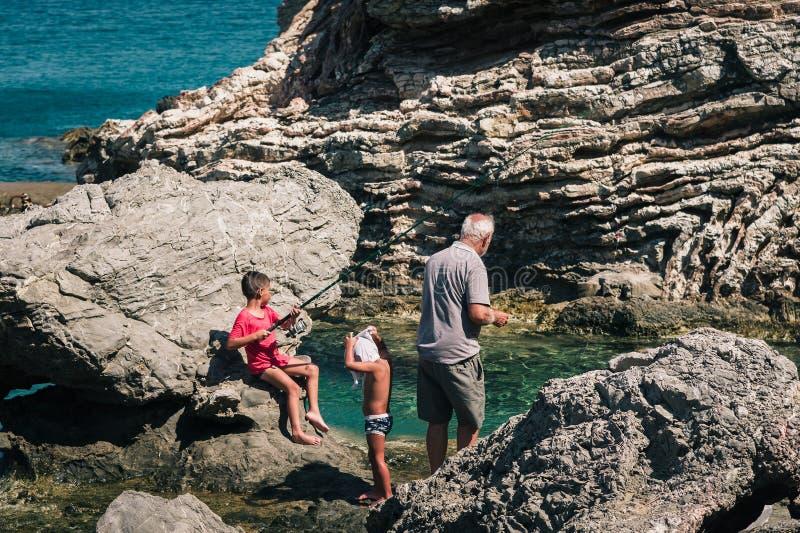 De oude mens vangt vissen samen met zijn jonge kleinzonen royalty-vrije stock afbeeldingen