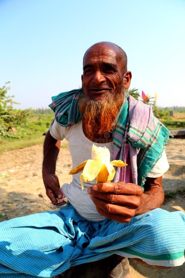 De oude mens zit met banaan royalty-vrije stock afbeelding