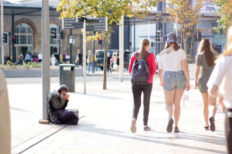 De oude mens zit op een straat en speelt voor geld stock fotografie