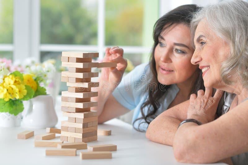 De oude mensen spelen een raadsspel stock afbeelding