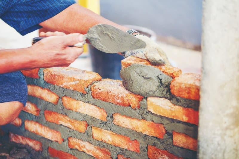De oude mensenhand vergoelijkt het cement gebouwde nieuwe huis van de muurbaksteen, Baksteen stock fotografie