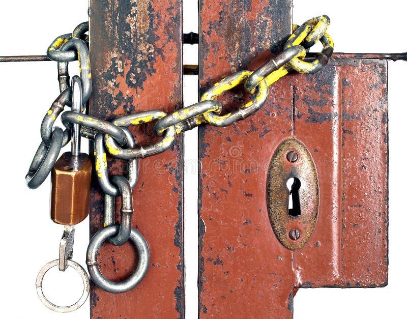 De oude de metaalketting en sleutel hangen gesloten smeedijzerpoorten op witte achtergrond stock foto
