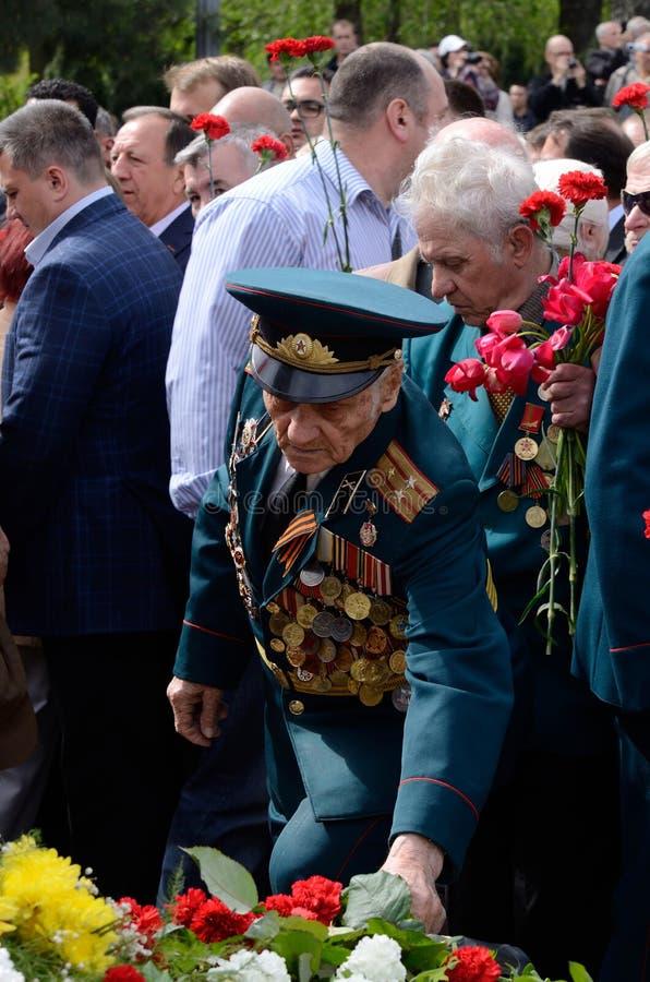 De oude militair komt gezette bloemen aan Eeuwige Vlam tijdens viering Victory Day in herdenking van Sovjetmilitairen royalty-vrije stock foto's