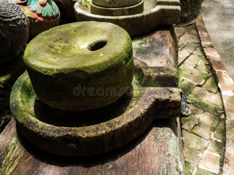 De oude molensteen heeft rond groen korstmos en Oude molensteen gezet op oude houten raad stock afbeeldingen