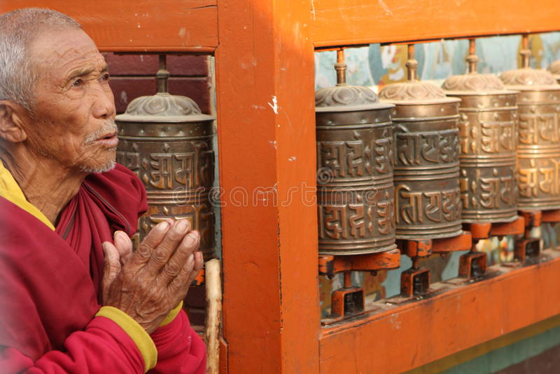 De oude monnik leest mantra dichtbij biddend molens stock foto's