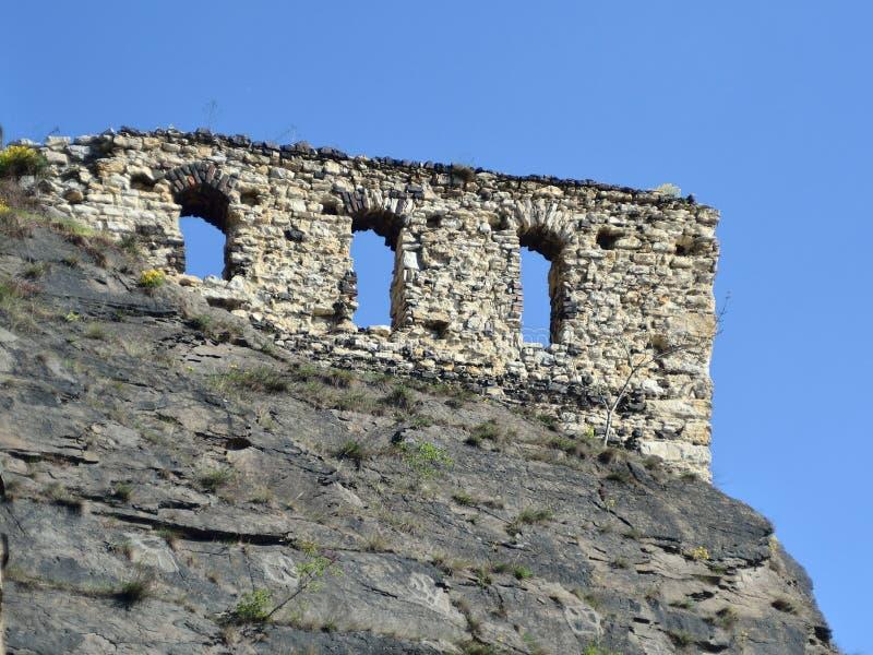 De oude muren op de rots stock afbeelding