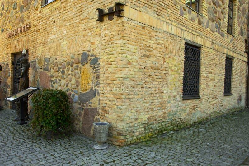 De oude de muurhoek van het baksteenhuis met de poorten van de boogvorm en steelt barvensters royalty-vrije stock afbeeldingen