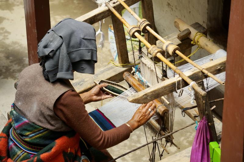 De oude Nepalese vrouw vlecht manueel de mat op een oud eigengemaakt weefgetouw, in de stad van Lo Mantang stock foto