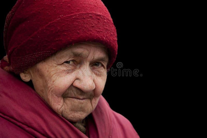 De oude oma in rode headscarf met het doordringen kijkt royalty-vrije stock fotografie