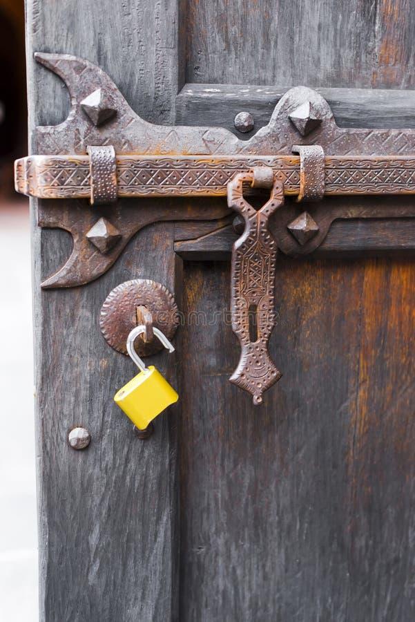 De oude open houten deur sneed gesmeed deadbolt open gehechtheids modern geel hangslot stock fotografie