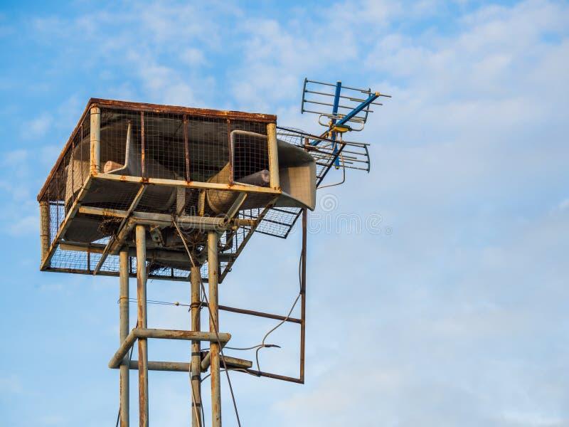 De oude openbare luidsprekers zenden uitstekende stijl op hoge toren uit de blauwe hemelachtergrond stock foto's