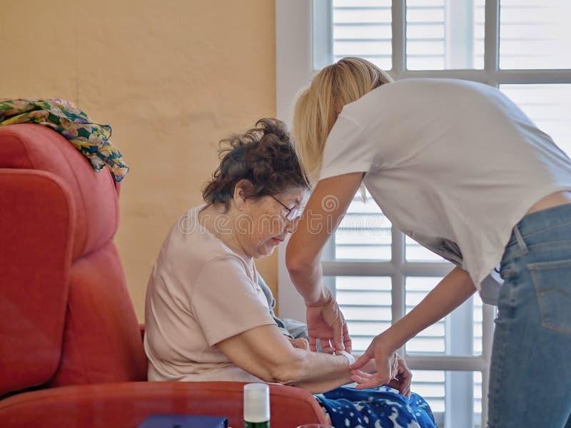 De oude oudste in haar vleugelstoel en geriatrische verpleegster helpt haar om een wond met pleister te behandelen stock afbeelding
