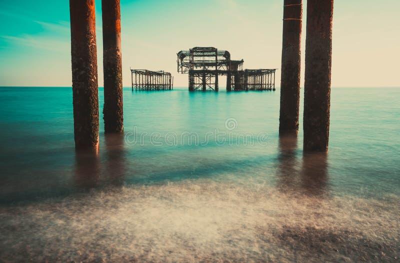 De oude overblijfselen van Brighton Pier verlieten status in overzees met mooie golven in Brighton en hesen het Westenpijler Oude stock afbeelding