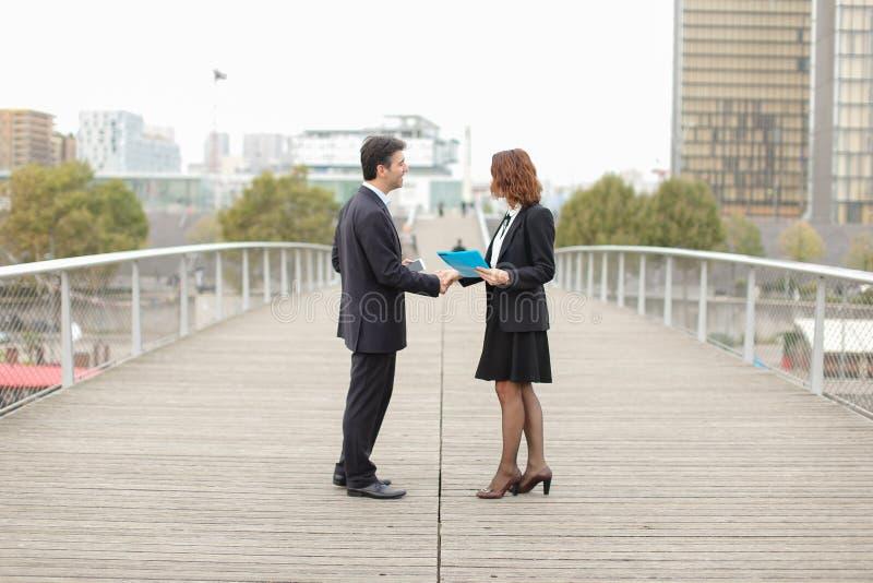 de oude IT partnersman met smartphone en de vrouw komen samen stock afbeelding